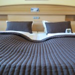 Zwei Einzelbetten, die wie ein Doppelbett aussehen im Upstalsboom Landhotel Friesland