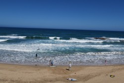 Am Strand von Lu Bagnu auf Sardinien gibt es im Wasser einige Felsen