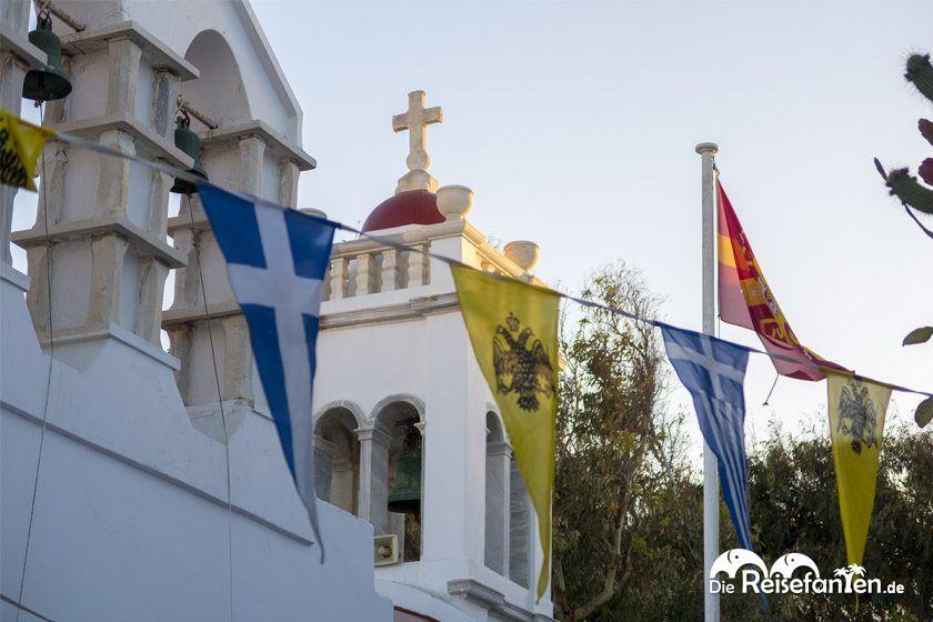 Fahnen und ein Kirchturm in Mykonos Stadt