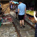Touristen und Einheimische besuchen den Mae Klong Markt