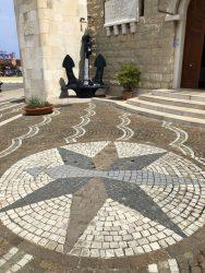 Kompass am Hafen von Bari