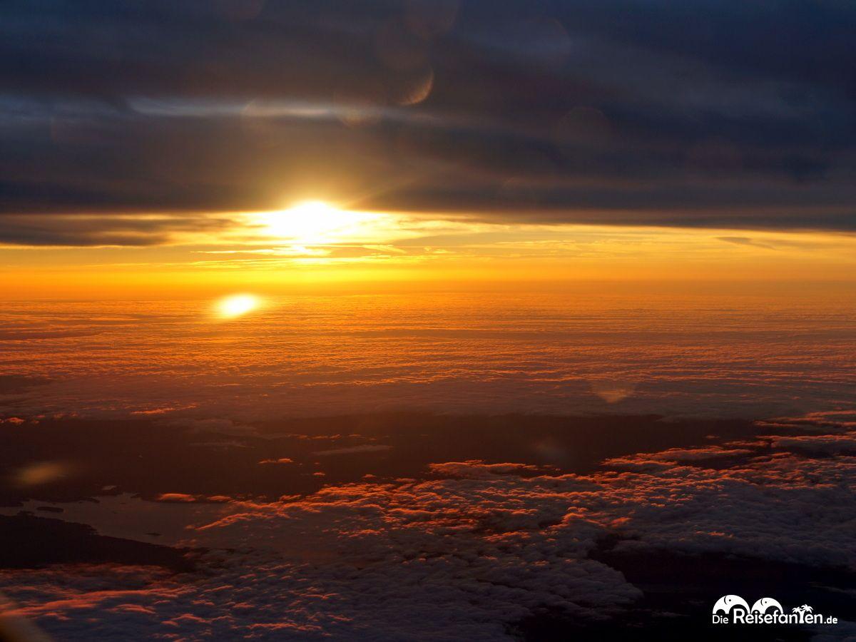 Zwischen Himmel und Erde die Sonne aus dem Flugzeug heraus fotograftiert