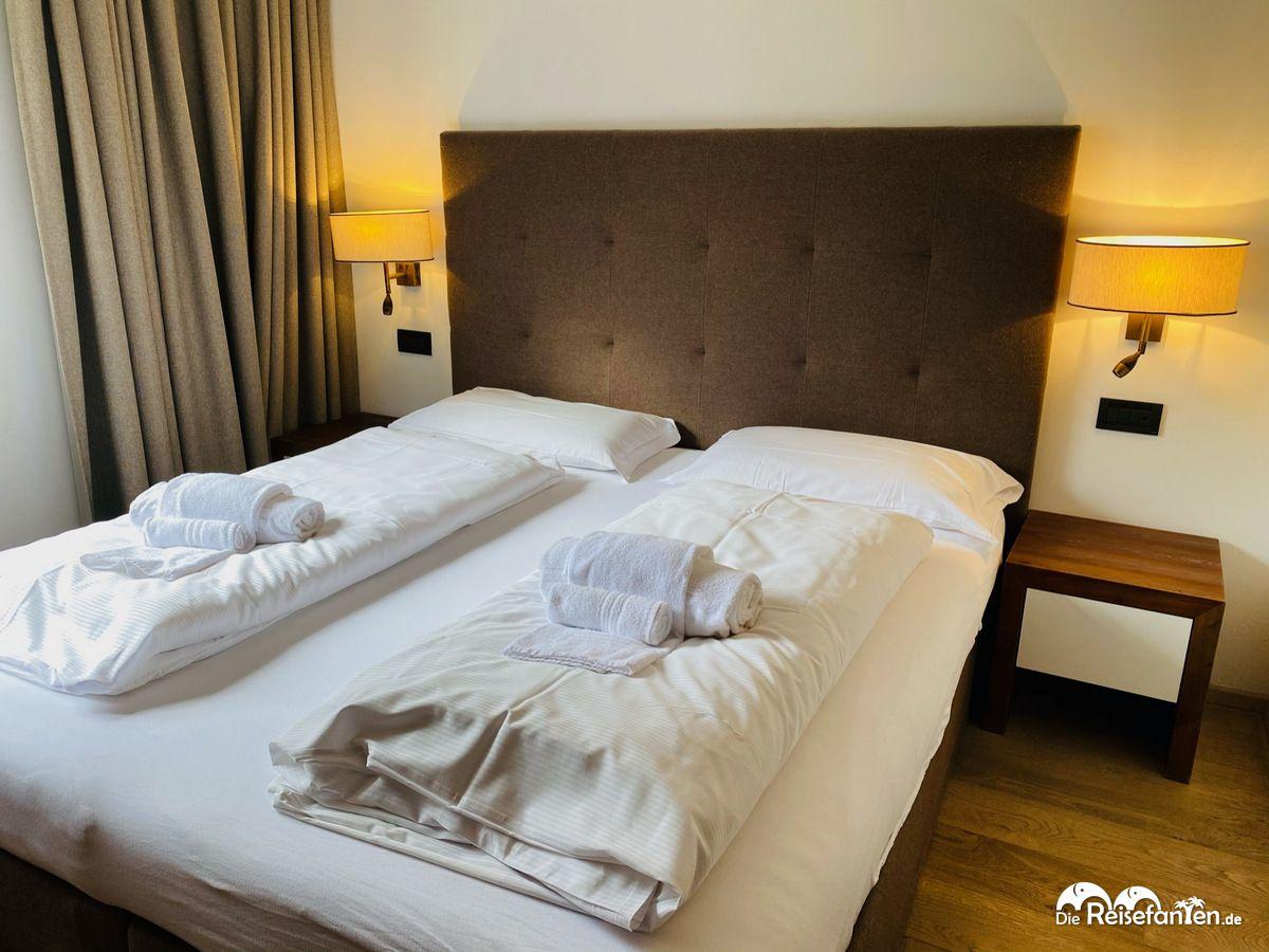 Gemütliches Doppelbett in der Ariston Dolomiti Residence in Toblach in Südtirol